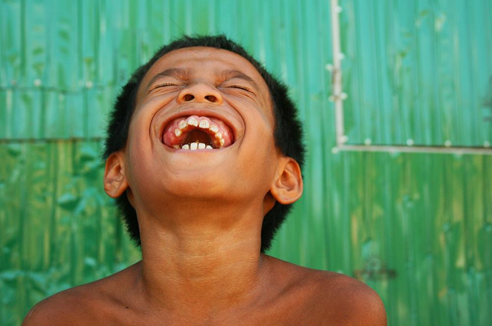 """En HIV-positiv gutt ler - uvitende om sin dystre fremtid. Fra boken """"Smertens smil - en reise i Kambodsja"""" av John Einar Sandvand"""